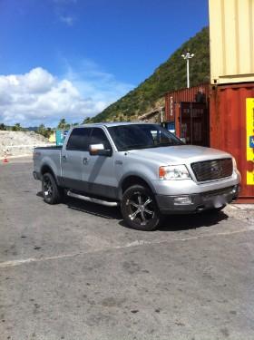 Auf dem Parkplatzareal am Flughafen Sint Maarten treten die Zielpersonen Händchen haltend laufend an einen amerikanischen Pick-Up-Truck heran. Bildrechte: DSD Detektiv SYSTEM Detektei ® GmbH / Randel